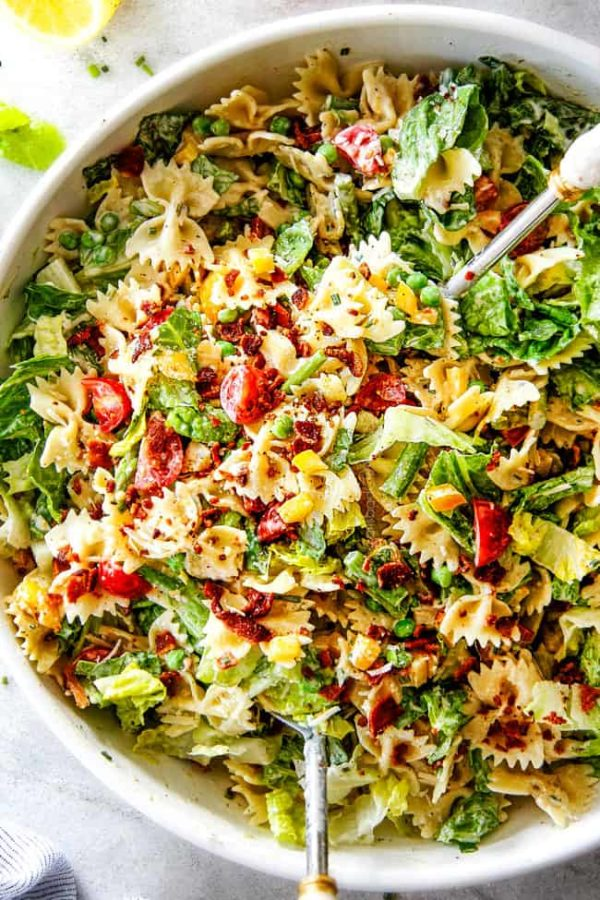 Top Shot of Best BLT Pasta Salad in a white bowl with white tongs lifting the salad up