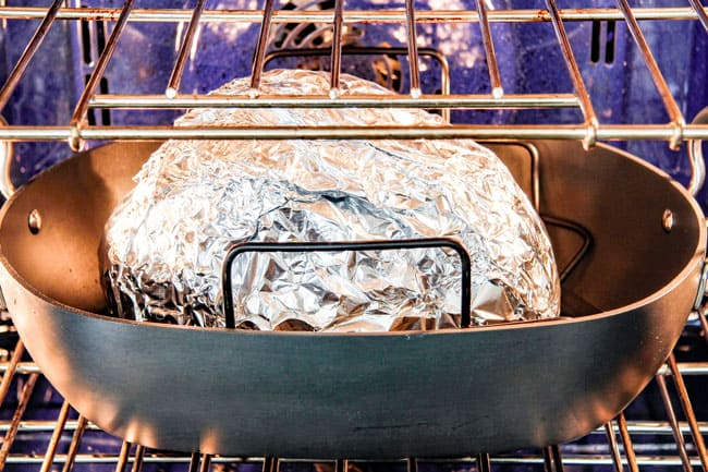 Showing How to Cook a Precooked Ham by placing foil covered ham in roasting pan on a roasting rack
