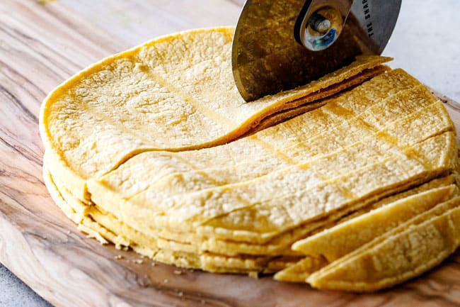 Showing How to Make Tortilla Strips for Chicken Tortilla Soup by cutting corn tortillas on a cutting board with a pizza cutter