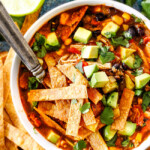 a white bowl of Chicken Tortilla Soup loaded homemade tortilla strips, avocados, sour dream