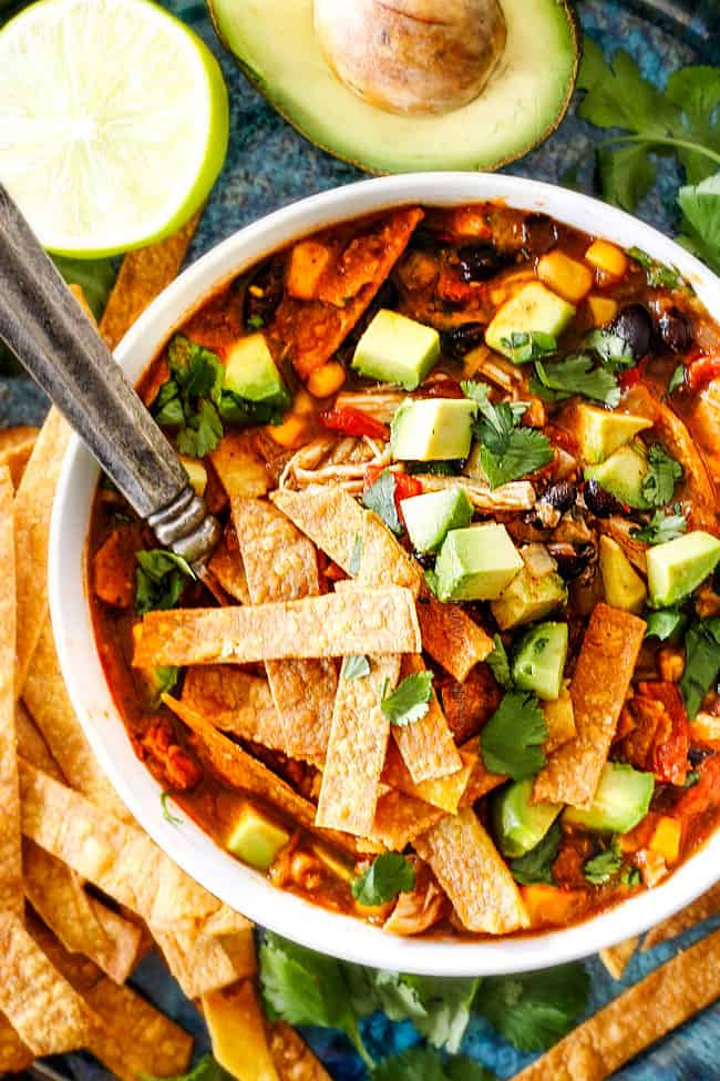 a white bowl of Mexican Chicken Tortilla Soup loaded homemade tortilla strips, avocados, sour dream