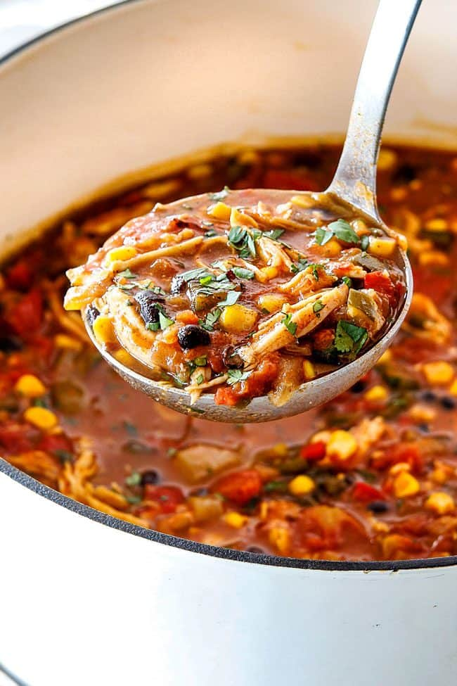 Up close of ladeful of easy Chicken Tortilla Soup in a white dutch oven with a spoonful of soup loaded with chicken, beans, corn, and tomatoes
