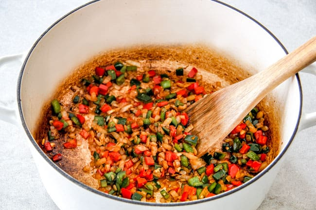Showing How to Make Chicken Tortilla Soup by sauteinig onions, garlic, red bell peppers, poblano peppers and onions