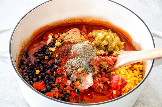 Showing How to Make Chicken Tortilla Soup by adding chicken, fire diced tomatoes, black beans, corn, enchilada sauce, chicken broth, chili powder, cumin, smoked paprika, dried oregano, salt and pepper to white Dutch oven