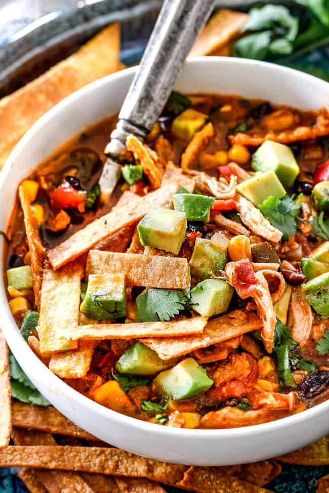 Up close of a spoonful of chicken tortilla soup loaded with avocados, tortilla strips, black beans and corn