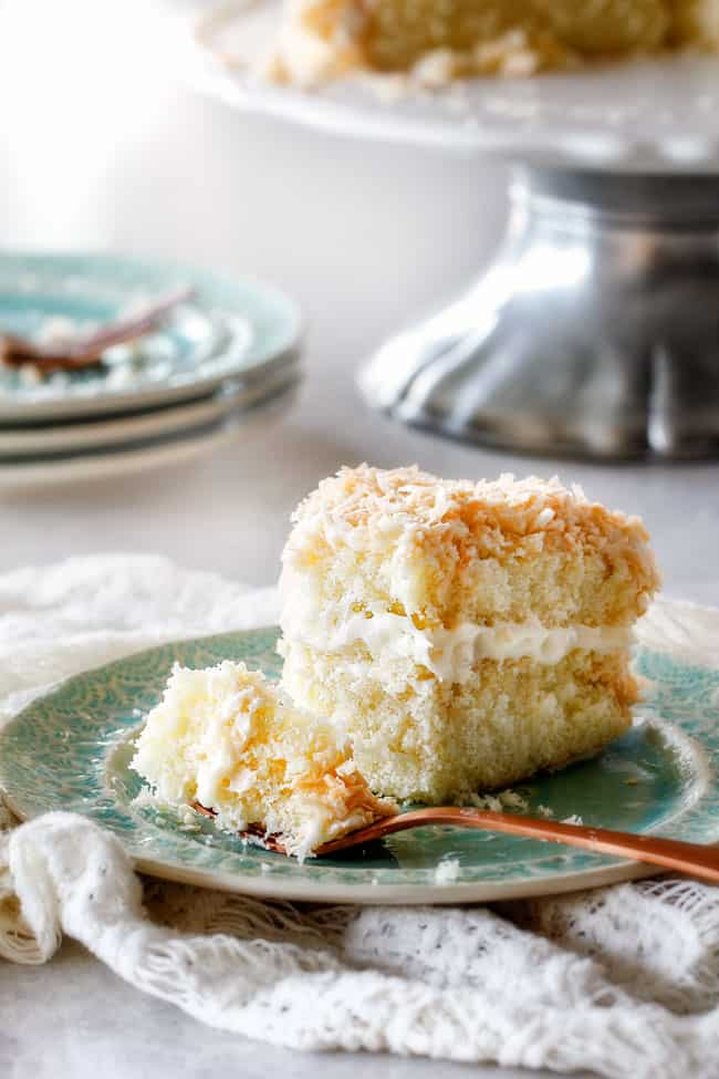 far away shot of simple Coconut Cake with a fork on the plate with a bite of cake on it