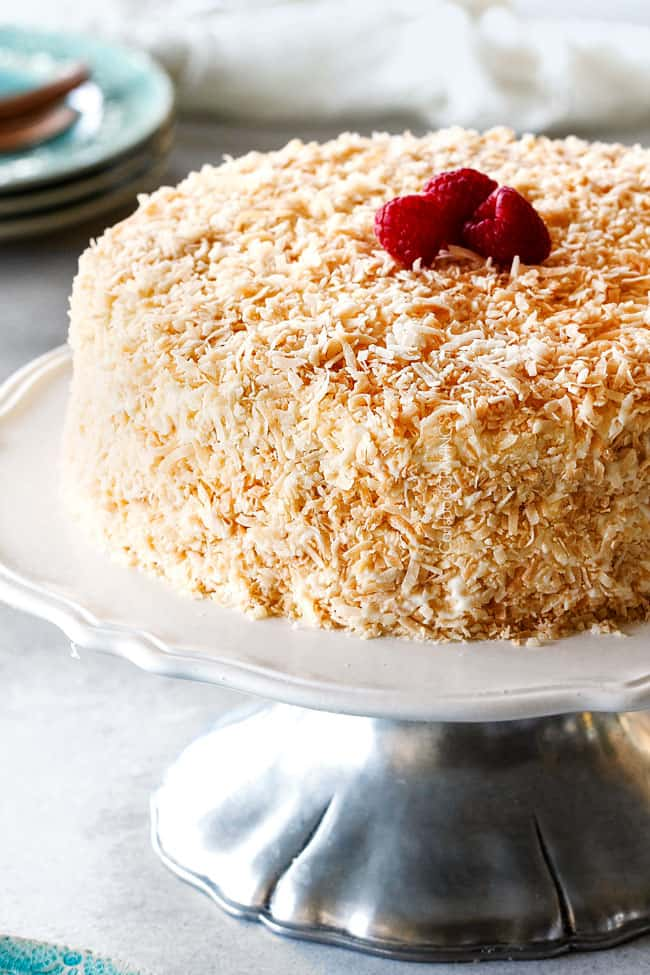 Best Coconut Cake on a white cake stand with toasted coconut