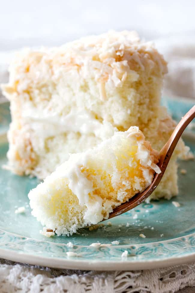 up close shot of easy moist Coconut Cake with a fork of cake on a silver plate