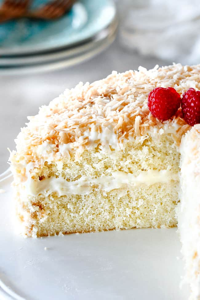 homemade Coconut Cake with a slice cut out looking at ceneter of cake with cream