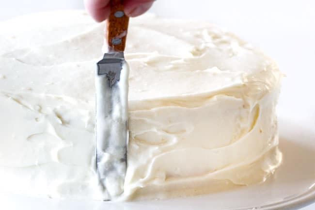 How to make easy Coconut Cake by frosting top and all sides with Coconut frosting