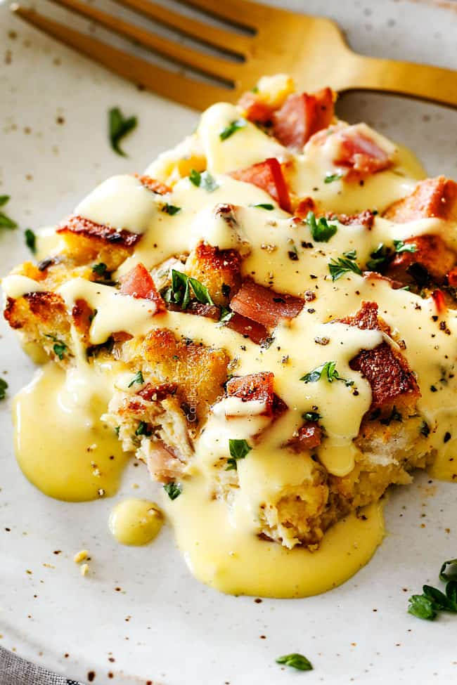 Eggs Benedict Casserole on a speckled plate being smothered by Hollandaise Sauce