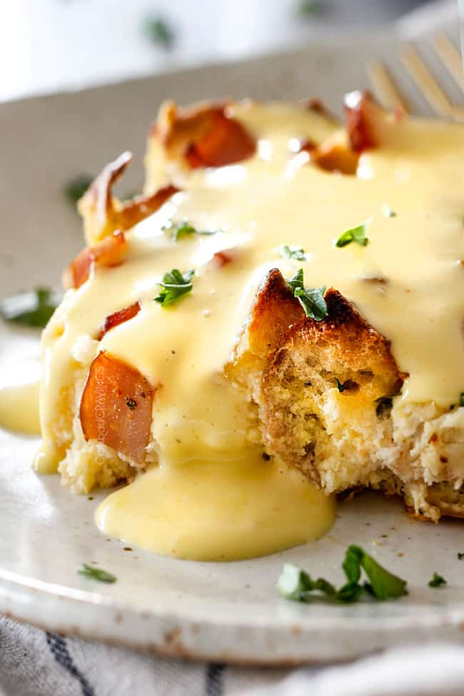 up close shot of Eggs Benedict Casserole on a speckled plate being smothered by Hollandaise Sauce
