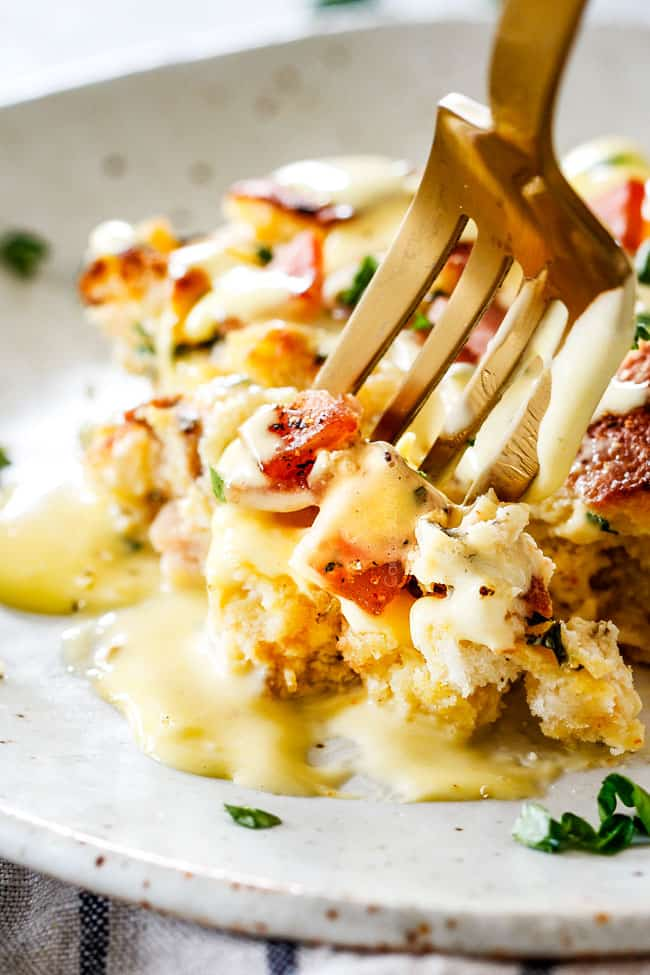 Up close shot of easy Eggs Benedict Casserole on a speckled plate with a fork taking a bite