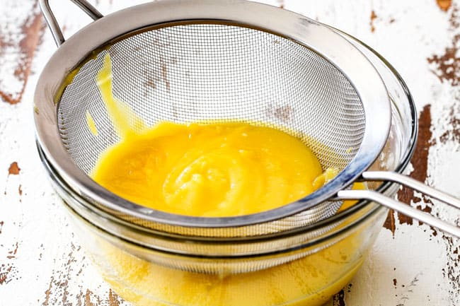 Showing how to make Lemon Curd for Lemon Blueberry Cake by straining lemon curd in a fine mesh sieve over a glass bowl