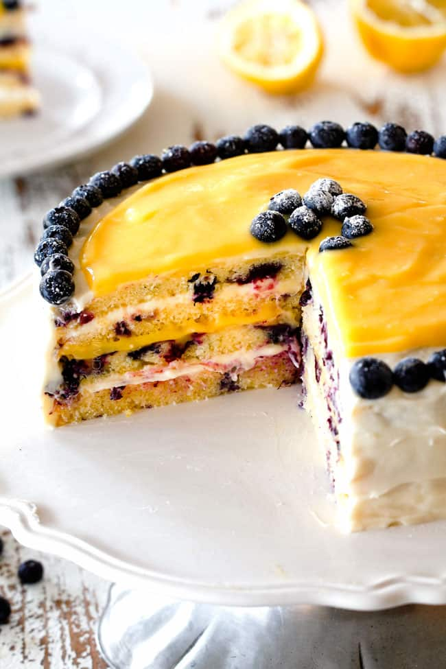 moist Lemon Blueberry Cake with Lemon Curd with a slice cut out of it showing layer of cake with blueberries on a white pedestal