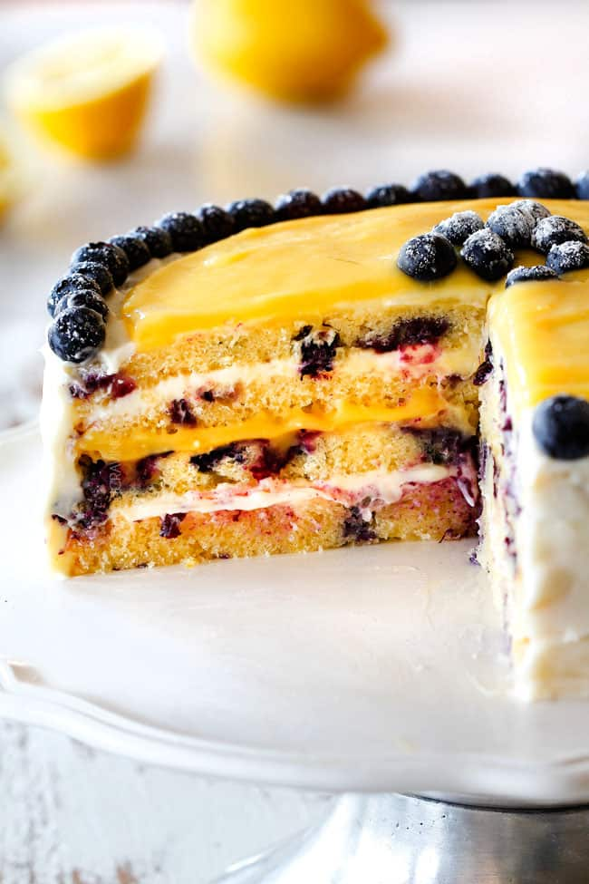 moist Lemon Blueberry Cake with Lemon Curd with a slice cut out of it showing layers of cake with lemon cream cheese frosting and lemon curd