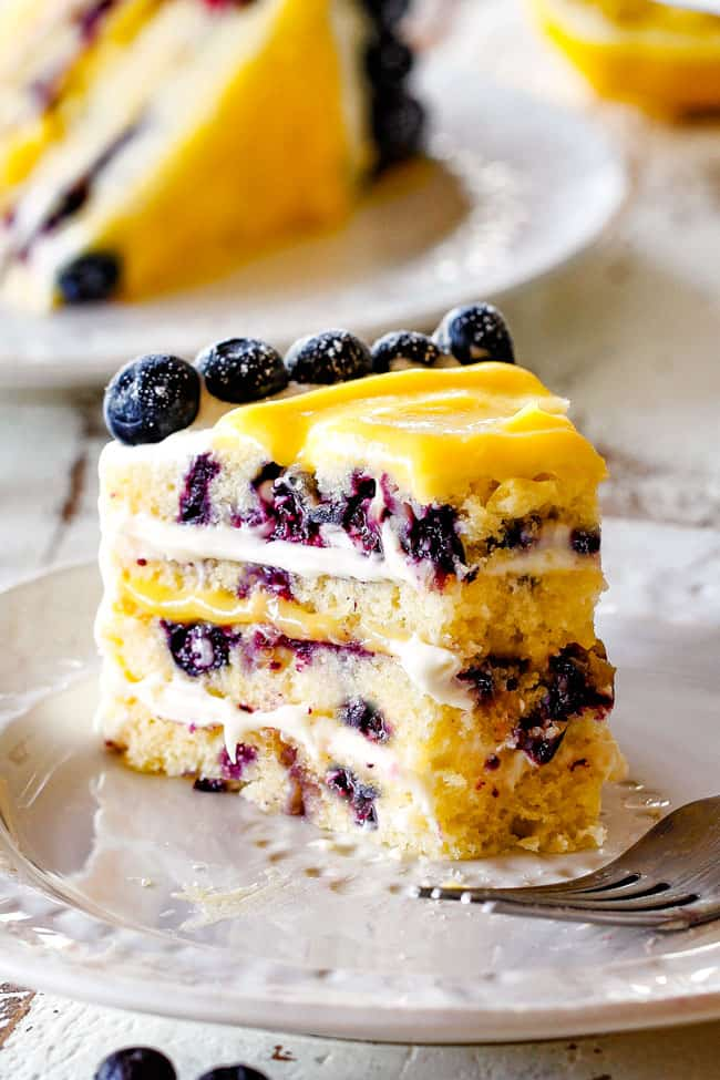 slice of lemon blueberry cake with a piece taken out of it sitting on a white plate