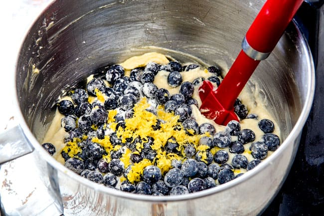 Showing how to make Lemon Blueberry Cake by adding blueberries and lemon zest to large metal mixing bowl with batter
