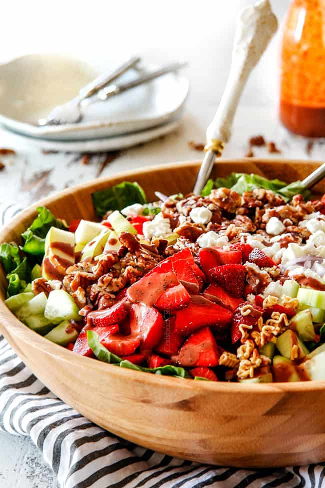 Side shot of best strawberry salad with Balsamic dressing in a wood bowl with white tongs