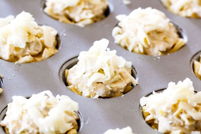 Showing how to make Artichoke Dip Bites by adding Artichoke Dips to puff pastry dough in muffin tin