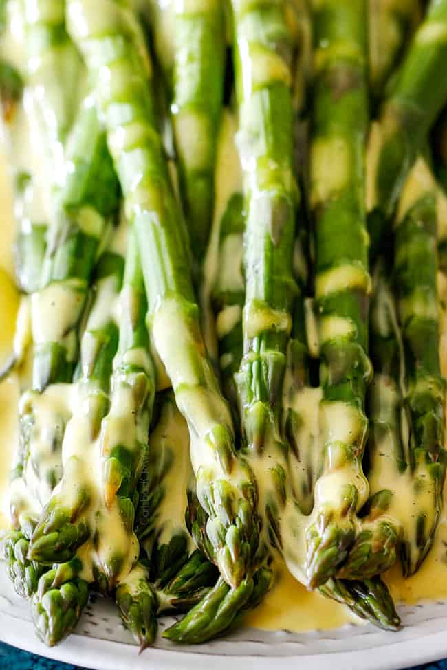 Up close of asparagus on a white platter that has been drizzled with Blender Hollandaise Sauce