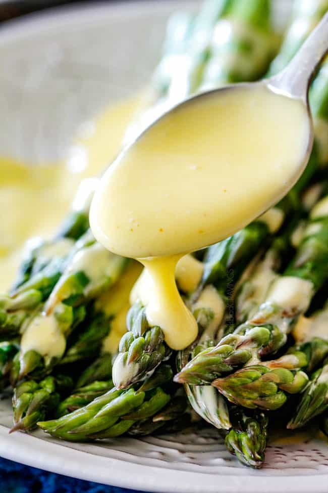 up close shot of spooning rich and creamy Blender Hollandaise Sauce on asparagus thats on a white platter
