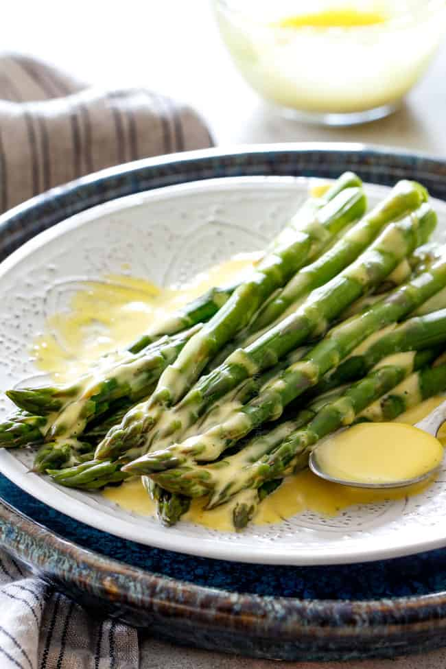 Far away shot of asparagus on a white platter that has been drizzled with easy Blender Hollandaise Sauce