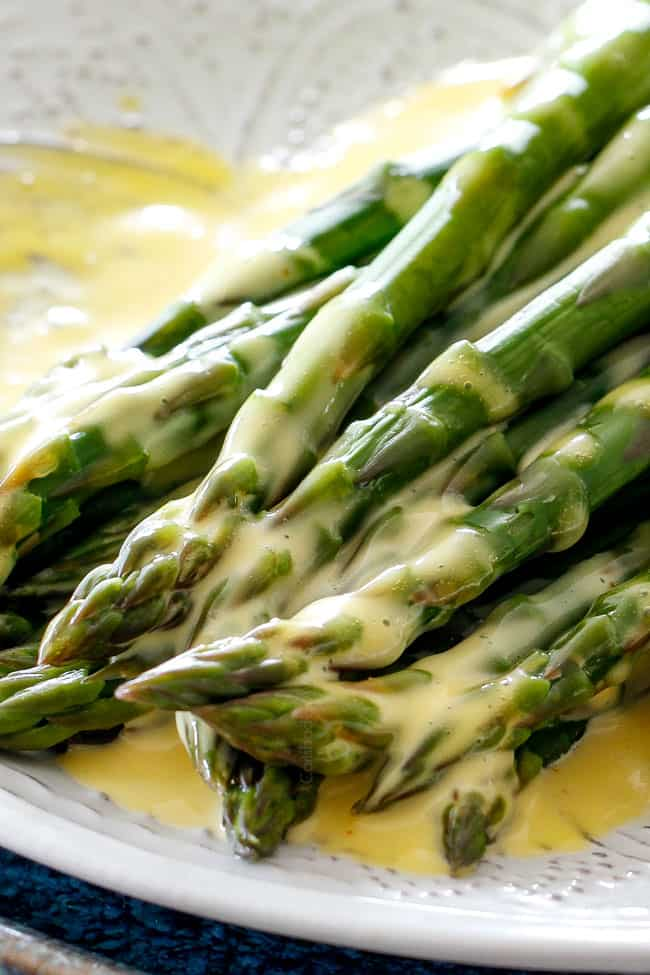 Up close shot of asparagus on a white platter that has been drizzled with easy Blender Hollandaise Sauce