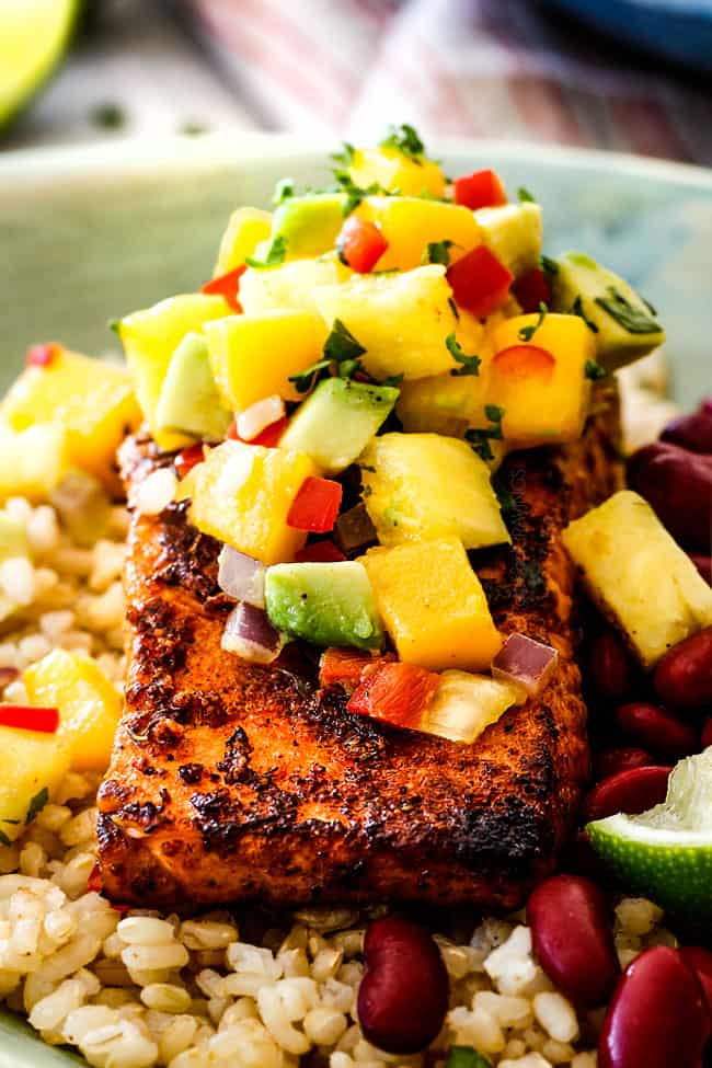 close up of pan seared cajun salmon in a green bowl with Pineapple, mango and rice