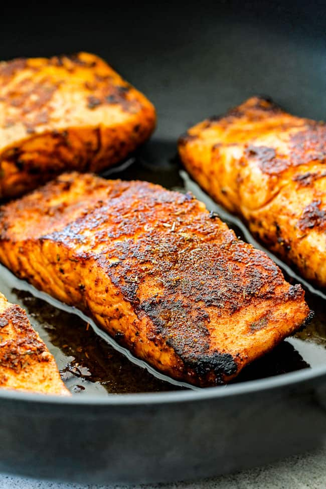 side view of cajun salmon in a black skillet being seared