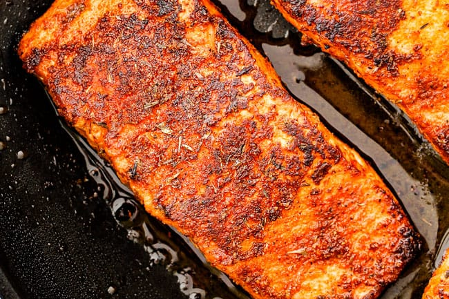 Cajun salmon in a black skillet being cooked