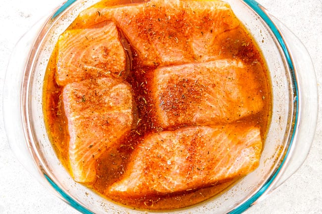 Cajun salmon marinating in a glass bowl with orange juice, lime juice and soy sauce