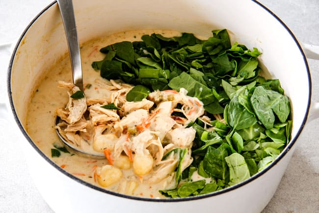 Showing how to make best Chicken Gnocchi Soup by adding spinach to soup with shredded chicken