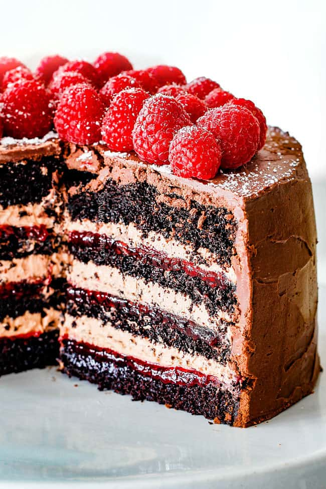 Chocolate Raspberry Cake with sliced removed showing layers of dark chocolate cake, raspberry jam filling, chocolate ganache and chocolate mousse