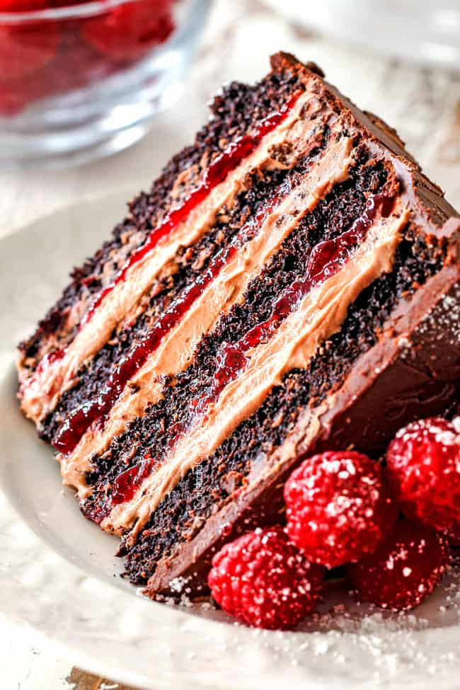 up close of a slice of moist Chocolate Raspberry Cake on its side showing layers of dark chocolate cake, raspberry jam filling, chocolate ganache and chocolate mousse