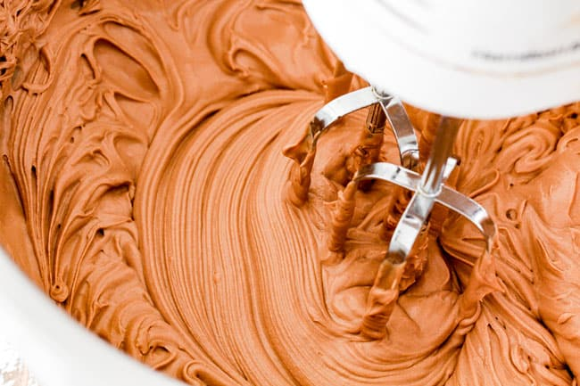 beating together chocolate ganache and mascarpone in a metal bowl for moist Dark Chocolate Raspberry Cake