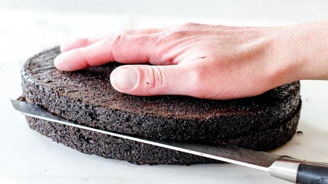 slicing moist Dark Chocolate Raspberry Cake in half to create layers