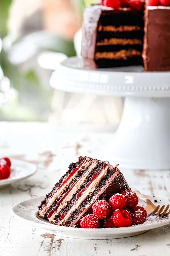a far away shot of a a slice of moist Chocolate Raspberry Cake on its side showing layers of dark chocolate cake, raspberry jam filling, chocolate ganache and chocolate mousse with the cake on a white pedestal in the background