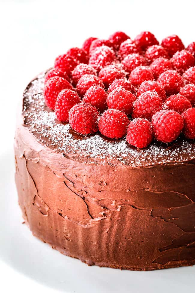 up close of easy Chocolate Raspberry Cake on a white pedestal with raspberries on top