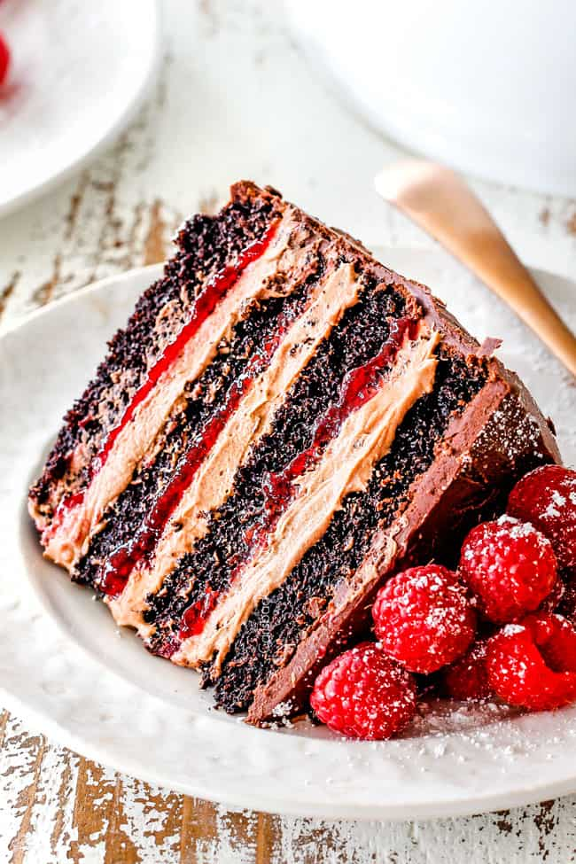 up close of a slice of Dark Chocolate Raspberry Cake on its side showing layers of dark chocolate cake, raspberry jam filling, chocolate ganache and chocolate mousse on a white plate with a gold fork