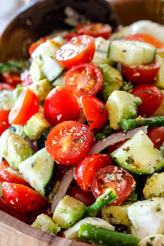 up close of Cucumber Tomato Salad recipe with cherry tomatoes, cucumbers, onion, asparagus and avocado