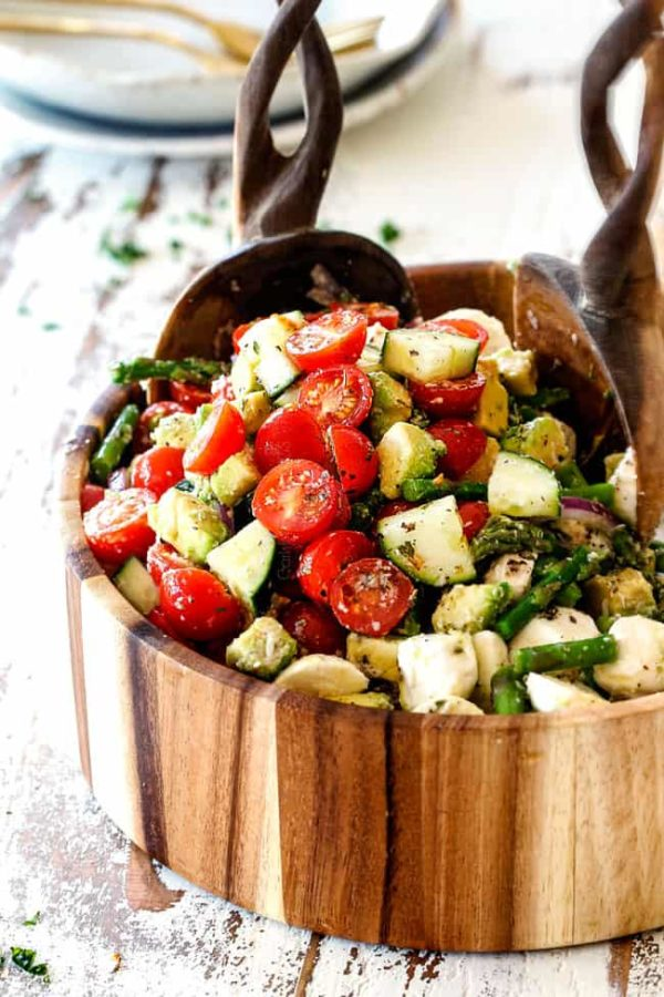 far away shot of Cucumber Tomato Salad recipe with cherry tomatoes, cucumbers, onion, asparagus and avocado in a wood bowl with wood tongs scooping salad