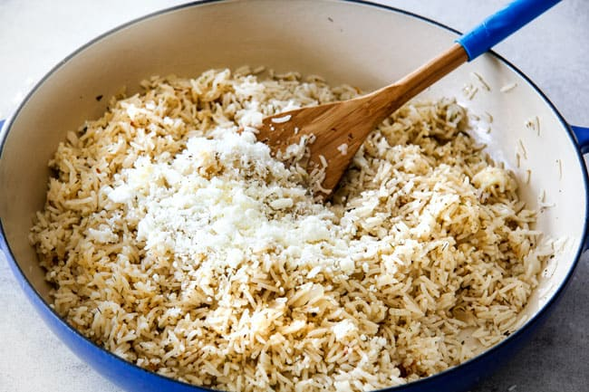 Showing how to prepare Lemon Rice by adding feta to cooked lemon rice in a blue skillet