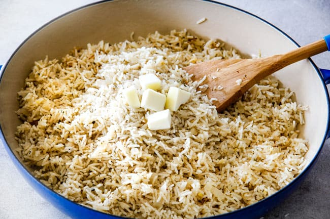 Showing how to prepare Lemon Rice by stirring in butter into cooked rice in a blue pot