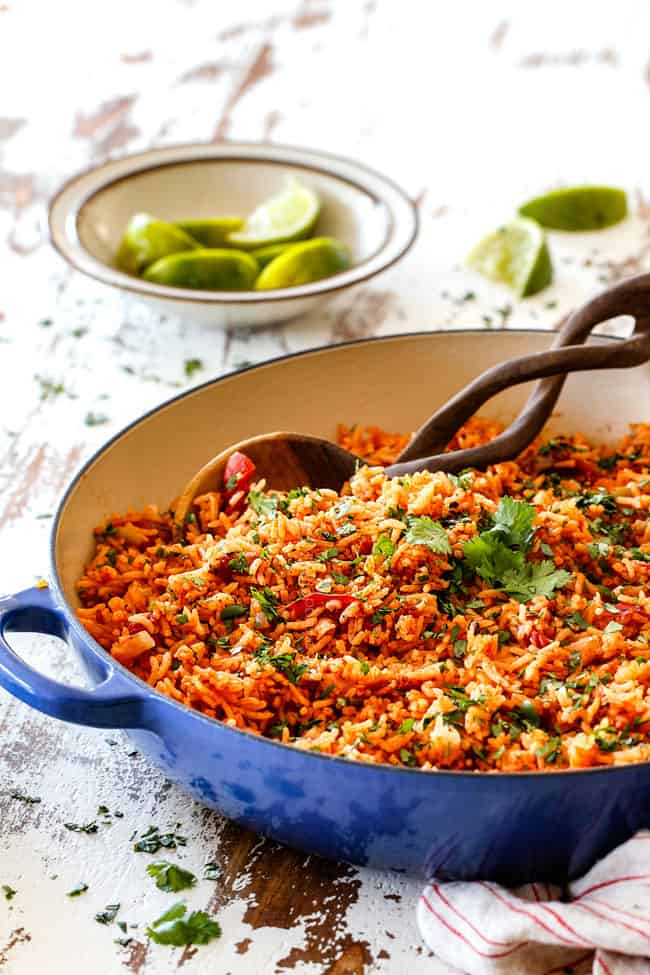 far away view of Restaurant style Mexican Rice on a white table in a blue skillet with limes