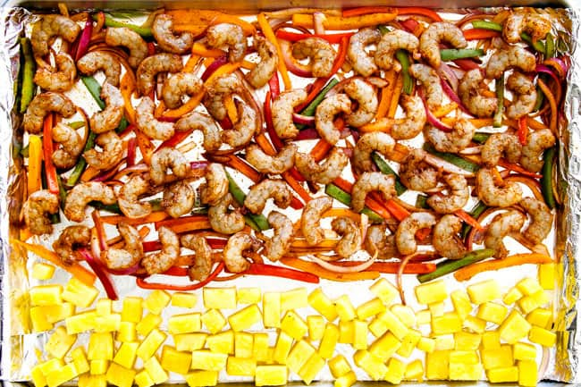 Showing how to make shrimp fajitas in oven by laying out shrimp on bell peppers and onions on a sheete pan