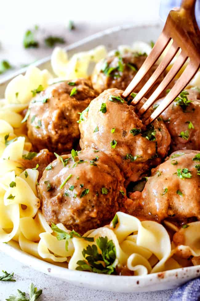 Swedish Meatballs with egg noodles on a plate with a fork sticking into a meatballs