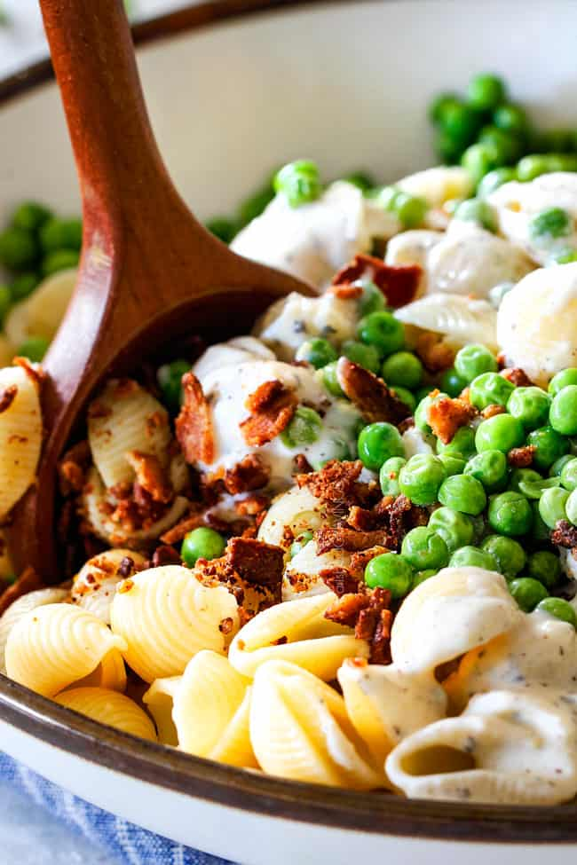 Showing how to make Creamy Pasta salad by stirring together macaroni, peas, bacon and dressing together