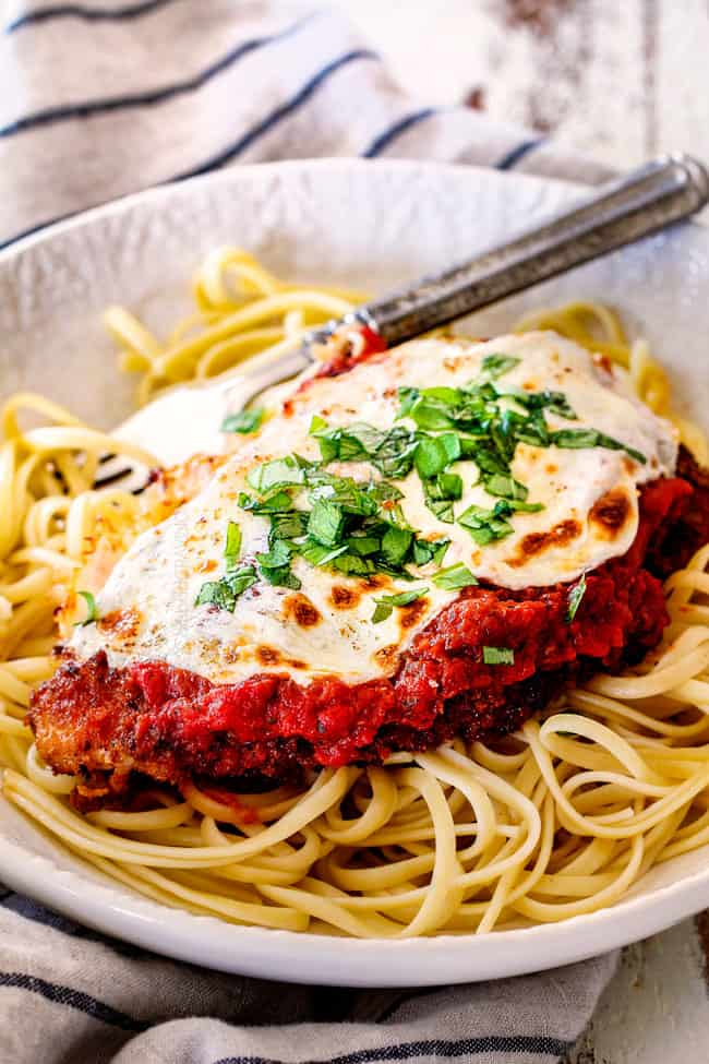 side view of a single piece of Chicken Parmesan on a bed of spaghetti on a white plate