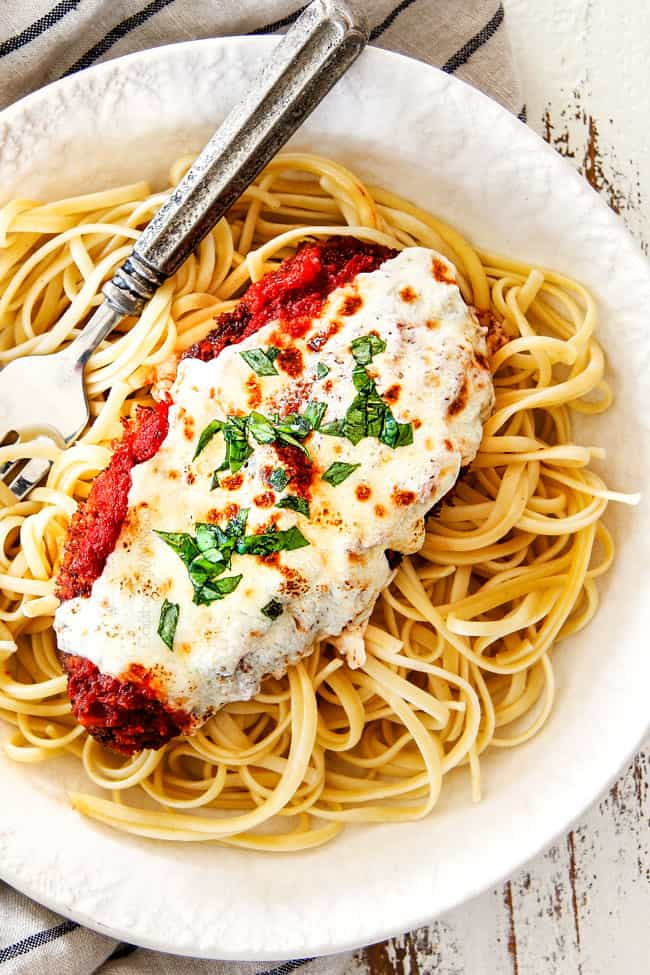 top view of a single piece of Chicken Parmesan on a bed of spaghetti on a white plate